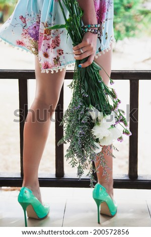 Close up fashion image of woman holding cute summer bouquet, wearing tender mint dress and neon green classic pumps. Vintage style. - stock photo