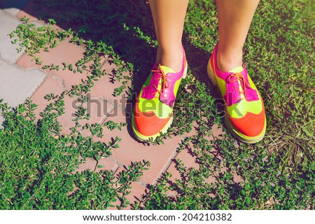 Close up fashion image of woman wearing bright neon hipster shoes,posing at city park.