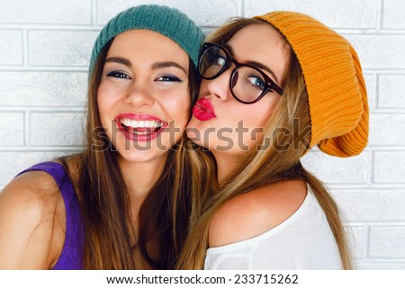 Close up fashion lifestyle portrait of two young hipster girls best friends, wearing bright make up and similar trendy hats, making funny faces and have gray time. Urban white brick wall background. - stock photo