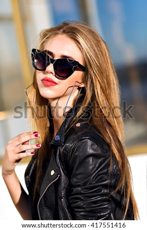 Close up fashion ;luxury portrait of stunning sexy woman, full perfect lips and face, sunny day sunglasses and leather jacket, big trendy earnings, grunge urban style. - stock photo