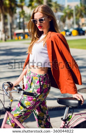 Close up fashion portrait of a young fashionable woman sitting on touring bicycle on Miami street during summer holidays, attractive funky female posing with bike for excursions against palm tree - stock photo