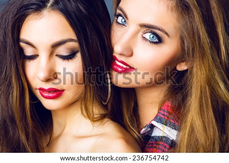 Close up fashion portrait of amazing sexy girls friends with bright make up and seductive full lips. Bright studio portrait of beautiful blonde and brunette women. - stock photo