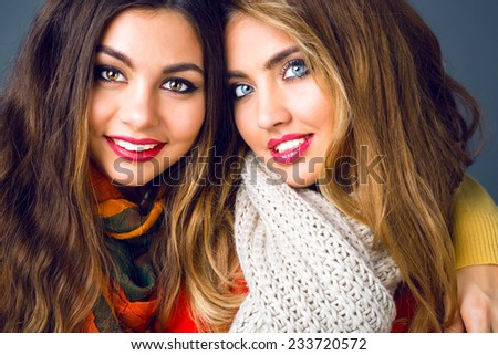 Close up fashion portrait of elegant lades with trendy makeup wearing stylish casual clothes and big warm scarfs. Fashion winter portrait of best friends sisters. Bright colors, grey background. - stock photo