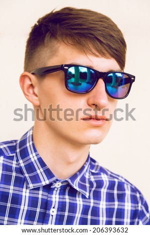 Close up fashion portrait of handsome stylish guy with cool modern haircut posing near beige wall in blue plaid shirt and navy mirrored sunglasses, not isolated, soft film colors. - stock photo