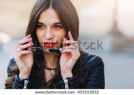 Close up fashion portrait of pretty seductive young woman with sunglasses, posing outdoor. Red lips, wavy hairstyle.  - stock photo