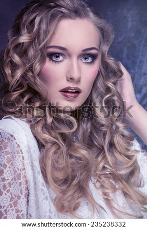 close-up fashion portrait of splendid blonde woman with long curly hair and stylish make-up wearing vintage elegant lace dress and looking in camera  - stock photo
