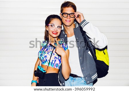 Close up fashion portrait of stylish young couple pretty woman and handsome man posing near white wall.  Retro camera,  bright crop top, perfect tan body. - stock photo