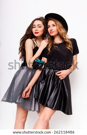 Close up fashion portrait of two elegant stylish  friends  wearing a leather  skirt and black hat , holding  retro camera.  Posing against white background. - stock photo