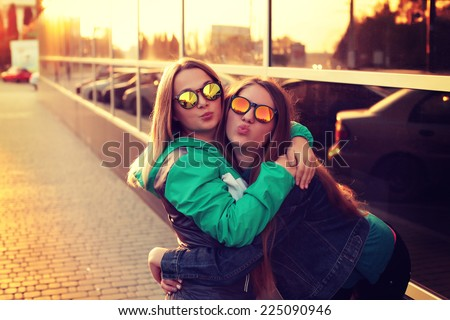 Close up fashion portrait of two young hipster girl friends, wearing mirrored sunglasses, having blonde and ombre hairs. Outdoors, lifestyle trendy photography with a retro vintage instagram filter. - stock photo