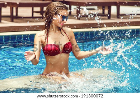 Close up fashion portrait of young beautiful woman making water splash in sexy bikini at the pool. - stock photo