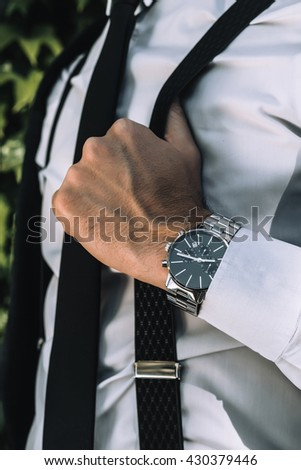 close up Fashion portrait of young businessman handsome model man in casual cloth suit with accessories on hands.closeup designer watches on businessman hand,penders,lifestyle - stock photo