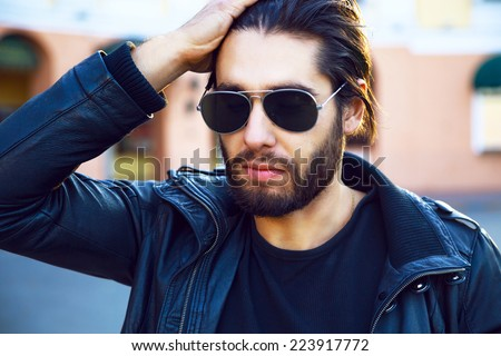 Close up fashion portrait of young hipster stylish handsome man wearing leather black rock maker and sunglasses, posing on the street, evening sunlight. - stock photo