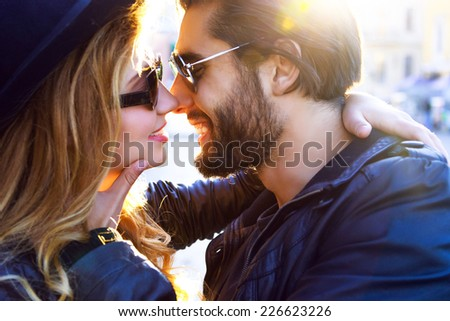 Close up fashion romantic portrait of young pretty couple kissing and hugs on the street at evening bright sunlight. Wearing leather jackets and sunglasses, rock style. - stock photo