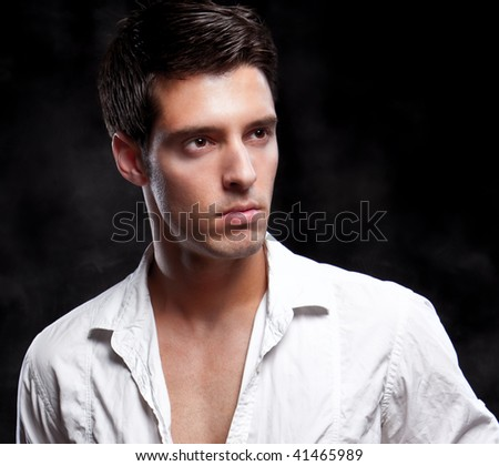 Close up Fashion Shot of a Young Man. A trendy European man dressed in contemporary white shirt. He is now a professional model - stock photo