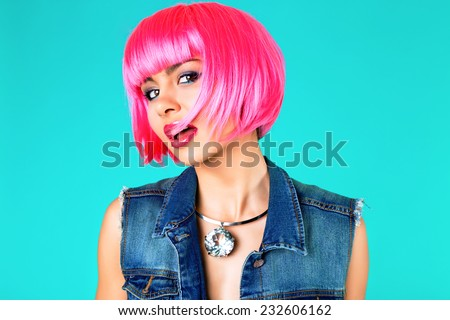 Close up fashion studio portrait of pretty young sensual woman wearing bright make up , neon pink party wig, denim vest and stylish massive diamond necklace. - stock photo