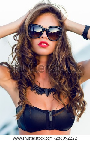 Close up fashion  summer  portrait of stylish  sexy  woman with perfect  tanned fit body   wearing trendy sunglasses   enjoying  pool party on luxury villa.  - stock photo