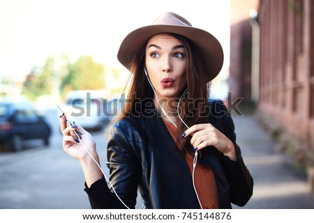 Close-up Fashion woman portrait of young pretty trendy girl posing at the city, autumn street fashion. Young woman calling phone with hands free and laughing - outdoor in street