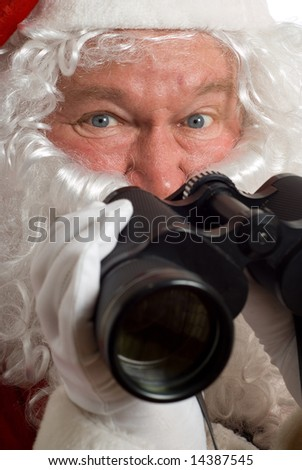 Close up Father Christmas with a questioning look in his eye and binoculars - stock photo