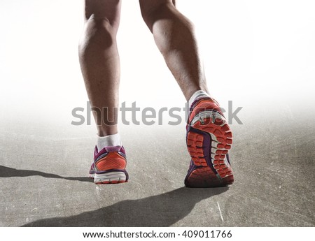 close up feet with running shoes and female strong athletic legs of sport woman jogging in fitness training workout on asphalt road design in advertising poster style - stock photo