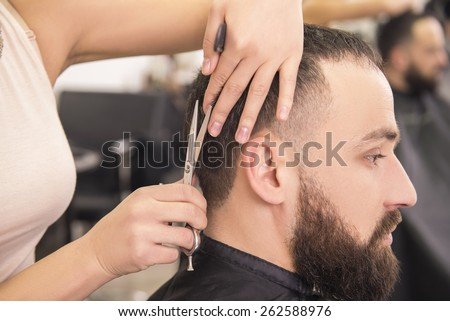 Close-up female hairdresser cutting hair of man client. - stock photo