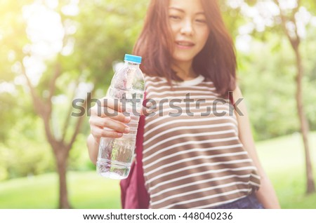 Close up female hand holding water while smiling at summer green park outdoor and bokeh nature background, healthy concept. - stock photo