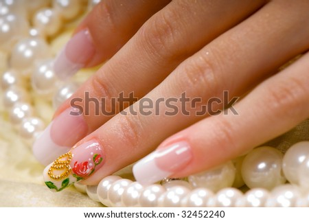 close-up female hand with a French manicure on a background of bright fabric and pearl