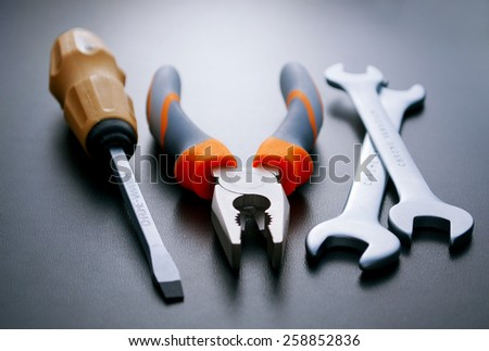 Close up Flathead Screw Driver, Combination Pliers and Open Ended Wrenches on a Gray Background - stock photo