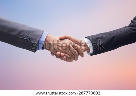 close up focus business man handshake on blurred colorful background:two adult man in suit outstretched arm hands shaking togetherness for agreement in promise concept:partner and colleagues concept - stock photo
