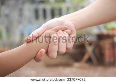 close up focus on hand:mother's hand holding little kid's hand for safe/healing and love concept:family love conceptual:helping hand:love of mom conception.intimacy affection kindness carefree concept - stock photo
