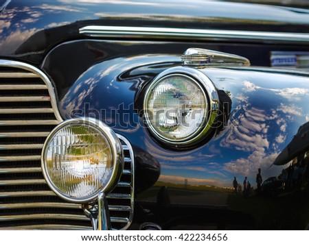 Close-up fragment of a black vintage car. Retro car. Headlights of vintage car. Selective focus. - stock photo