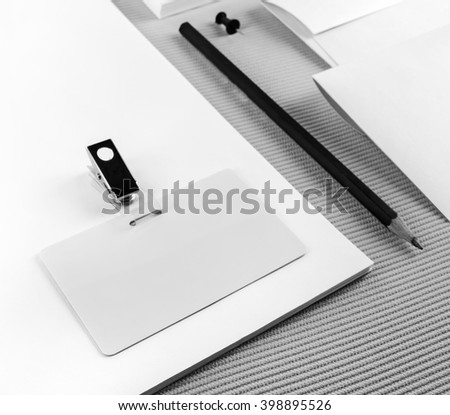 Close-up fragment of blank stationery and corporate identity set on gray background. Blank badge. Shallow depth of field. Selective focus.