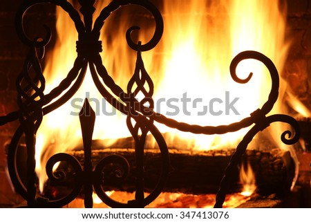close-up fragment of forged grate on a background of flames  - stock photo