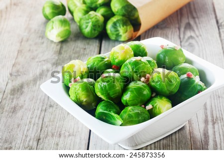 Close up Fresh Green Brussels Sprouts on White Bowl on Top of the Table - stock photo