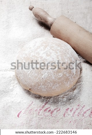Close up Fresh Homemade Pasta Dough Recipe on Table Filled with Flour and Wooden Roller on Side. - stock photo