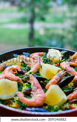 Close up fresh juicy prepared classic spanish dish paella with seafood, blue shell mussels, shrimps, rice with saffron spice, vegetables, tomatoes, smoked sausages and lemon with parsley in frying pan - stock photo