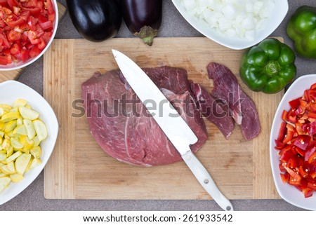 Close up Fresh Pork or Beef Meat on a Wooden Chopping Board with Knife Surrounded by Other Ingredients on Sides for Cooking Preparation Concept. - stock photo
