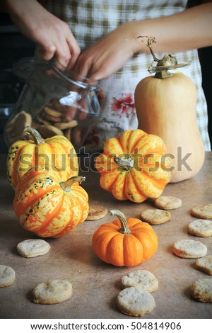 Close-up fresh pumpkins and cookies held by female in hands