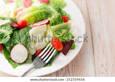Close up Fresh salad with tomatoes and beetroot on wood table - stock photo