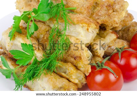 Close-up fried fish with cherry tomatoes on white plate. - stock photo