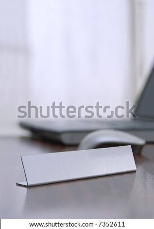 close up from a blank  nameplate with a  notebook and mouse defocused background