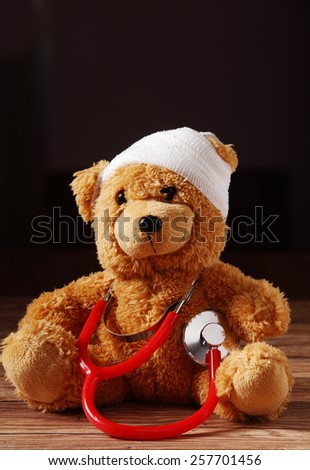 Close up Front View of Bandaged Plush Teddy Bear with Stethoscope Device on Top of the Wooden Table.