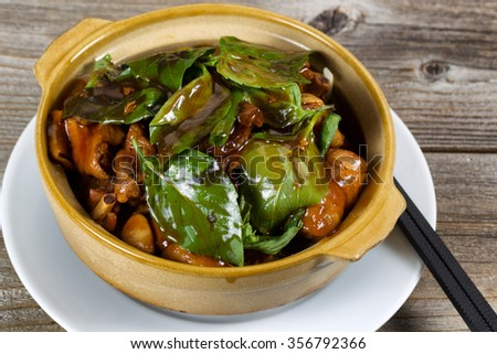 Close up front view of chicken and basil dish. Chopsticks on white plate underneath bowl on rustic wood background.  - stock photo