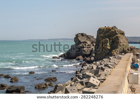Close up front view of sea port with stones and rock by the seacoast in sunny bright weather. - stock photo