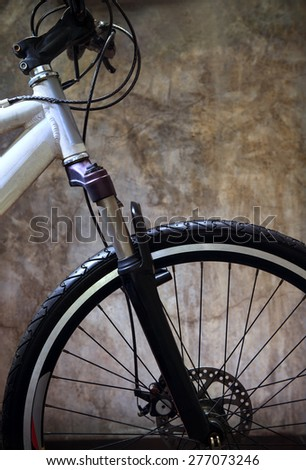 close up front wheel tire of mountain bike against grungy cement wall use for bicycle and biking conceptual