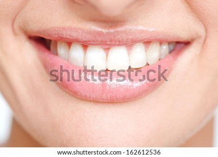 Close up frontal beauty section portrait view of a young woman natural smile with voluptuous pink lips and clean white teeth, detail.
