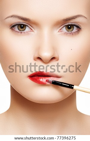 Close-up frontal portrait of beautiful woman model applying lipstick using lip concealer brush - stock photo