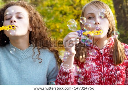 Close up frontal view of two teenager friends playing games together and blowing soap bubbles up in the air while in a natural park during a fall autumn sunny day, outdoors. - stock photo