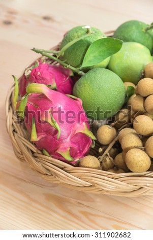 Close up fruit basket which contains longan, green citrus, dragonfruits on wood background - stock photo