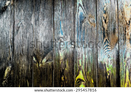 Close up full frame of rustic authentic wooden boards of floorboards or a fence, yellow and green tints visible in wood grain and knots - stock photo