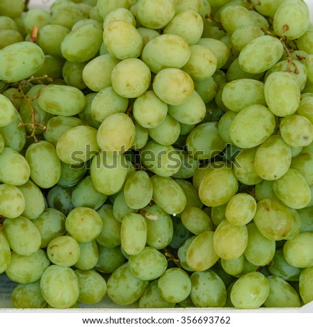 Close-up full frame view of fresh green grapes for sale at a local fruits market in Singapore. Natural food background - stock photo